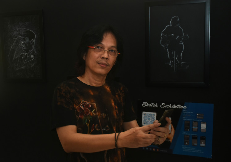 Guitarist Doddy Hernanto shows his sketches at the art exhibition.