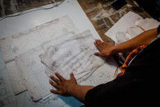 Subandi shows old sketches drawn on a piece of paper. JP/Anggertimur Lanang Tinarbuko