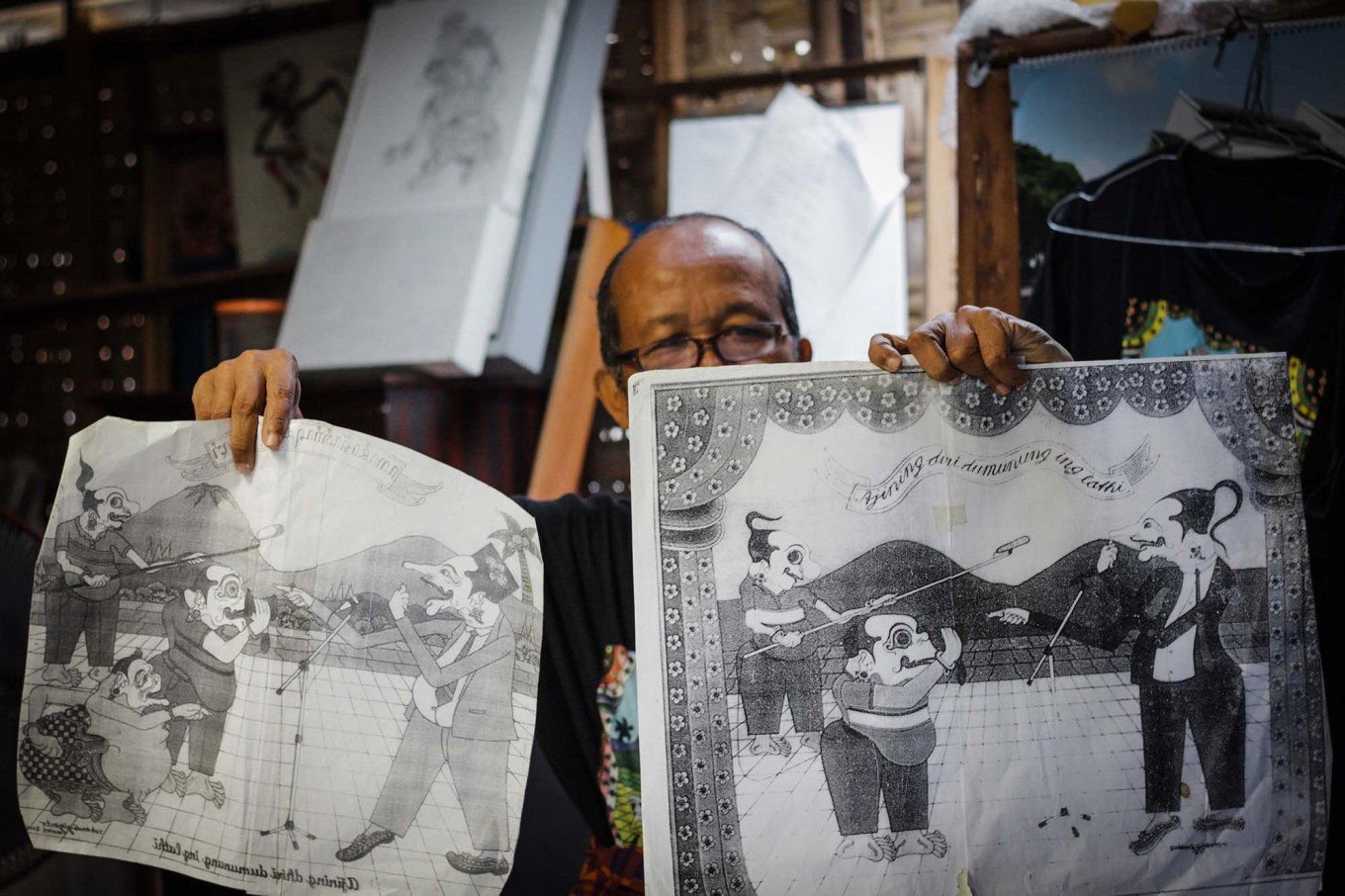 Subandi shows a copy of a glass painting that is now an archive of his work. JP/Anggertimur Lanang Tinarbuko