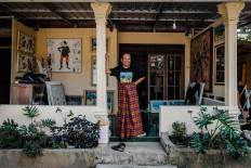 Subandi stands in his terrace, wearing a T-shirt and sarong which became his favorite clothes when painting. JP/Anggertimur Lanang Tinarbuko