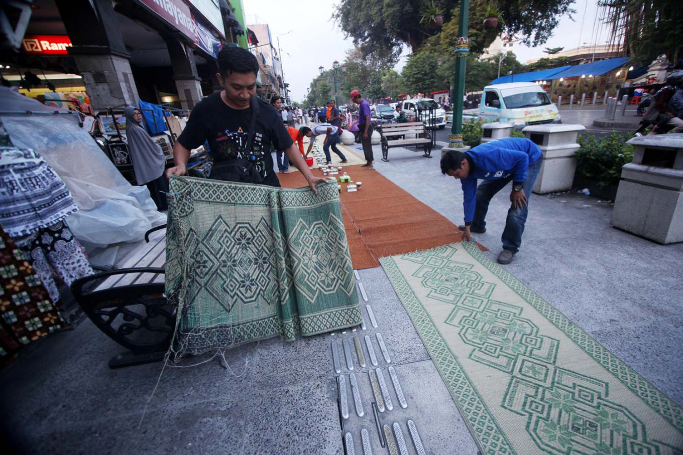 People lay out floor mats on which people will break the fast. JP/ Boy T. Harjanto