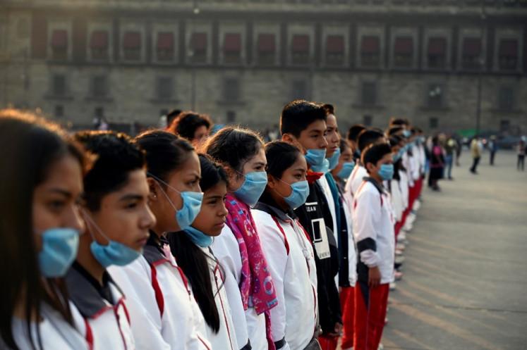 Un groupe d'étudiants porte des masques lors d'une cérémonie sur la place Zocalo à Mexico le 17 mai 2019.