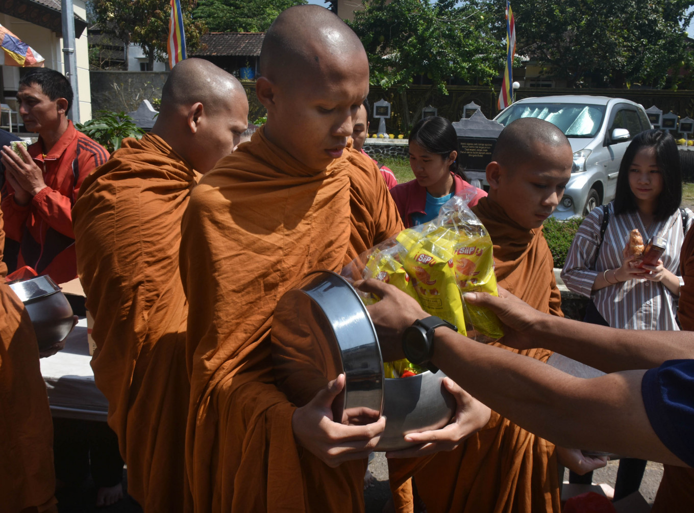 Novice monks receive alms from fellow Buddhists during the Pindhapata ritual at  Dhamadipa Arama Temple in Batu, East Java, on Monday. JP/Aman Rochman