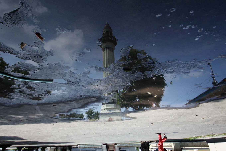 A reflection of a century-old minaret. JP/Boy T. Harjanto