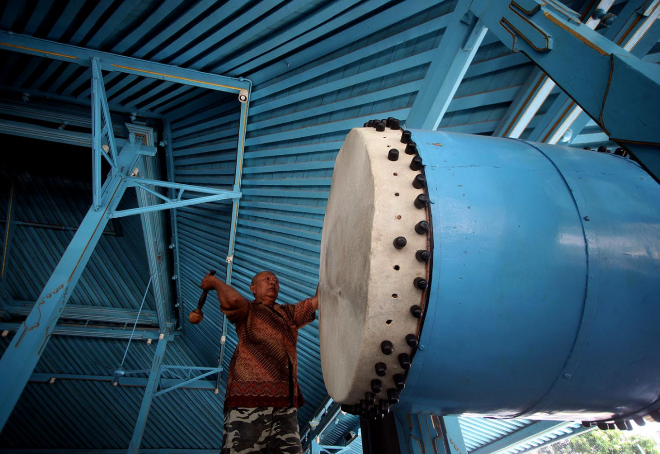 A mosque official hits the giant drum prior to the adzan (call to prayer). JP/Boy T. Harjanto