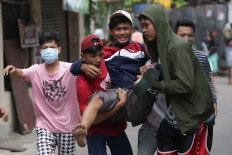 A protester is carried by his friends after getting shot by a rubber bullet in Jatibaru, Central Jakarta. JP/Wendra Ajistyatama