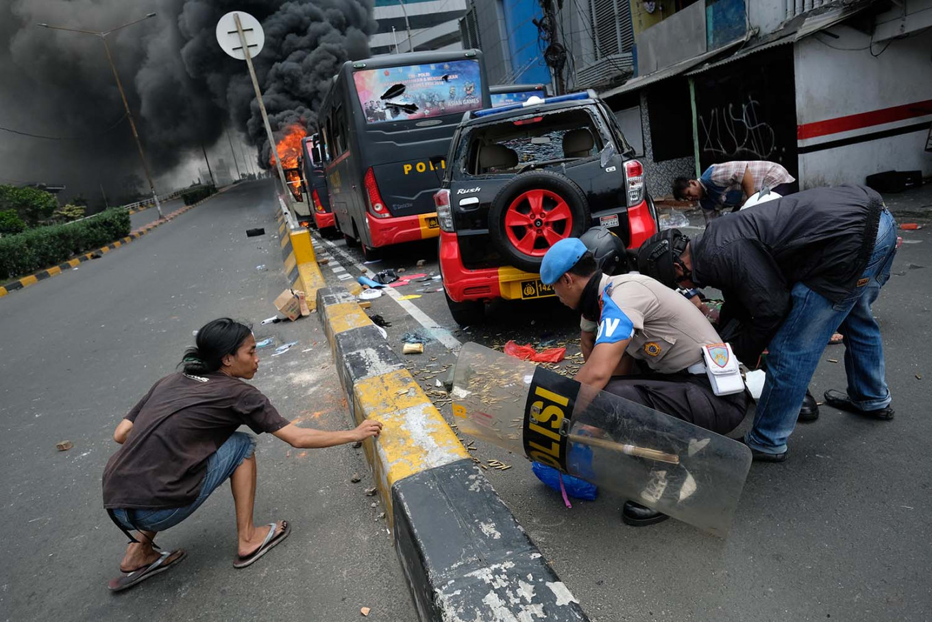 A young man helps policemen gather bullets from a police car damaged by rioters in Slipi, West Jakarta. JP/Jerry Adiguna