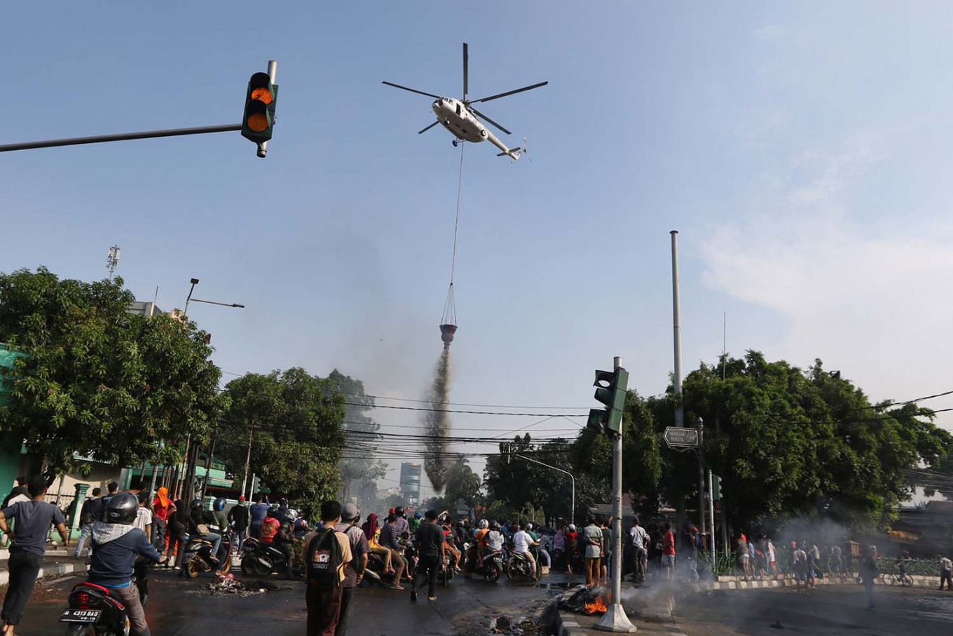 A helicopter water bombs the crowd in Petamburan, Central Jakarta. JP/Dhoni Setiawan