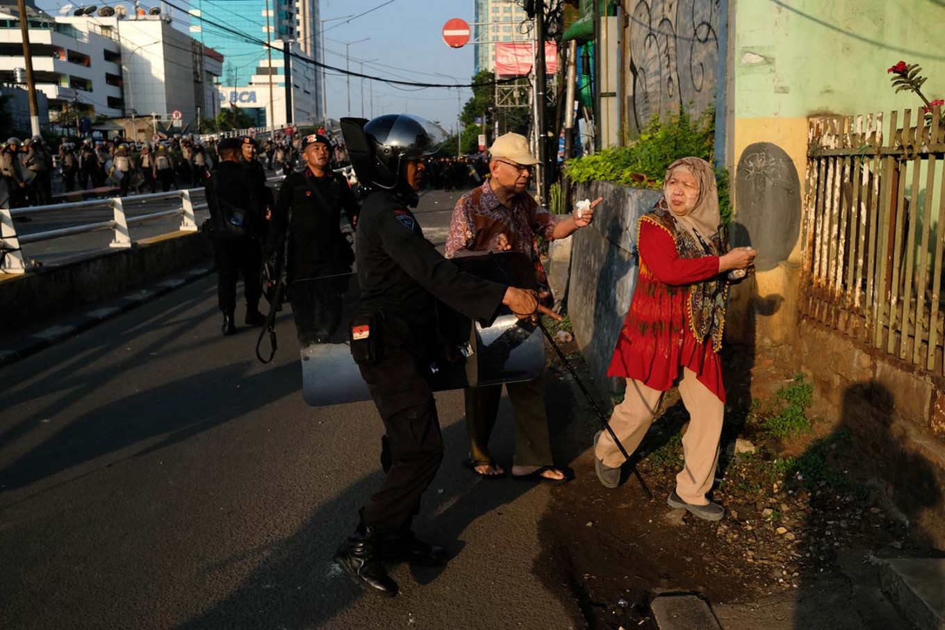 Mobile Brigade (Brimob) officers safeguard elders as they pass protestors on their way back to their home next to Slipi Market, West Jakarta. JP/Jerry Adiguna
