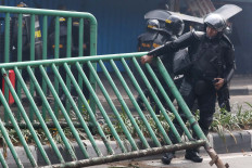 An antiriot policeman moves a damaged fence after a clash with protesters in Jati Baru, Central Jakarta, on Wednesday. JP/Dhoni Setiawan
