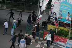 Rioters attempt to take down signs and banners in the Slipi area, West Jakarta. JP/Jerry Adiguna