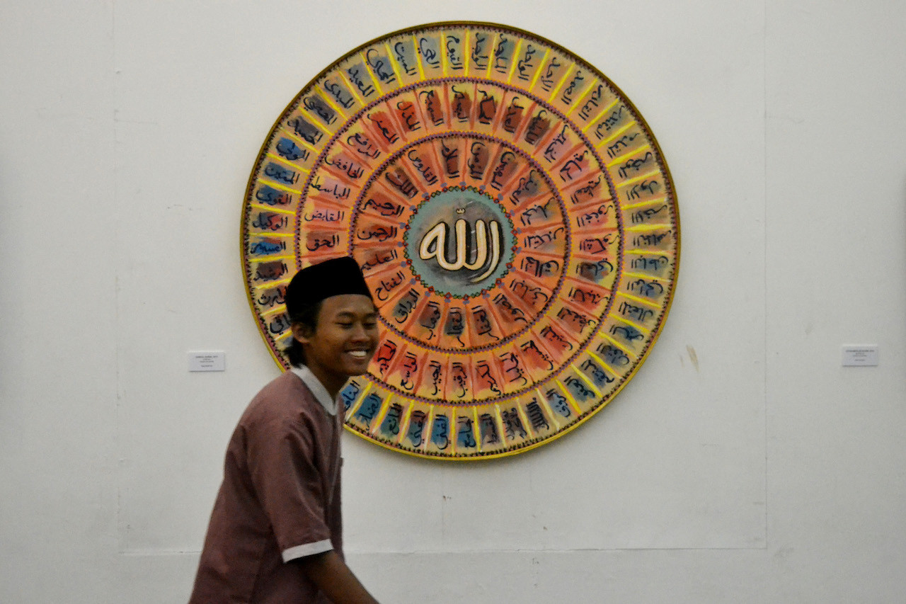A visitor to the Welas Asih (Compassion) calligraphy exhibition at Balai Soedjatmoko,Surakarta, walks past a painting by Toyib Bukhoeri titled 'Asmaul Husna' (99 beautiful names of God)