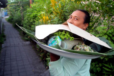 A man carries a giant tray packed with rice and side dishes, including the urap. JP/Zul Trio Anggono