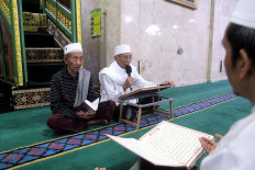 A cleric leads the Quran recitals prior to the Megibung event. JP/Zul Trio Anggono