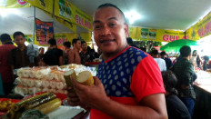 Homade: Bobby, a takjil seller, holds lemang(sugary rice cooked in hollowed bamboo). JP/ Budi Sutrisno