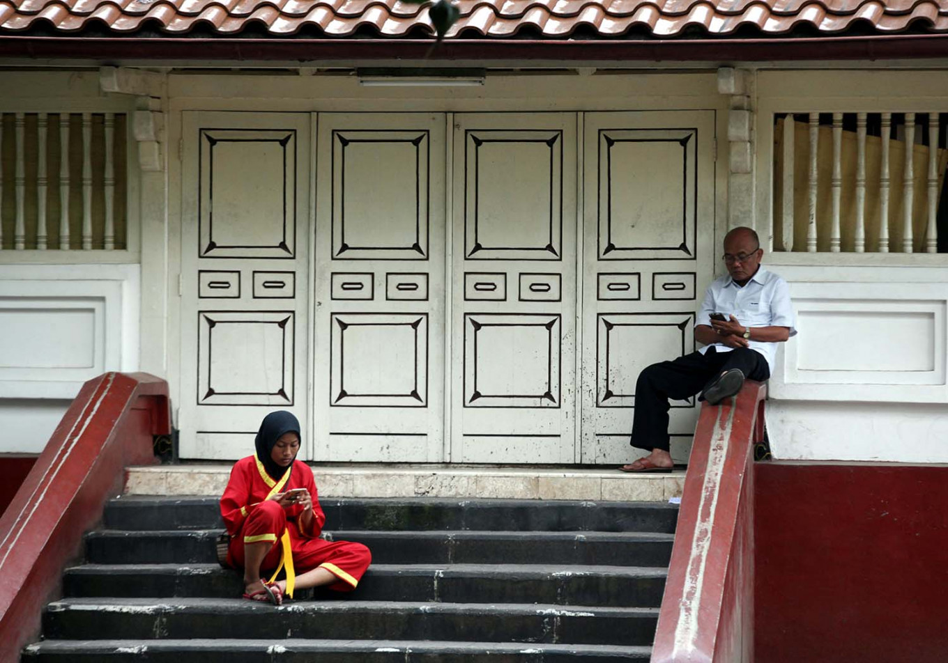 A teenage girl and an older man are busy with their mobile phones in front of Kauman mosque. JP/Boy T. Harjanto
