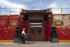"A cyclist passes a street with a wall that says ""Old town heritage"". JP/Sigit Pamungkas"