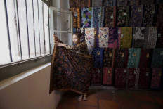 A shop attendant wears kebaya and batik fabric to meet customers at the Omah Batik Tiga Negri batik house in Lasem. JP/Sigit Pamungkas