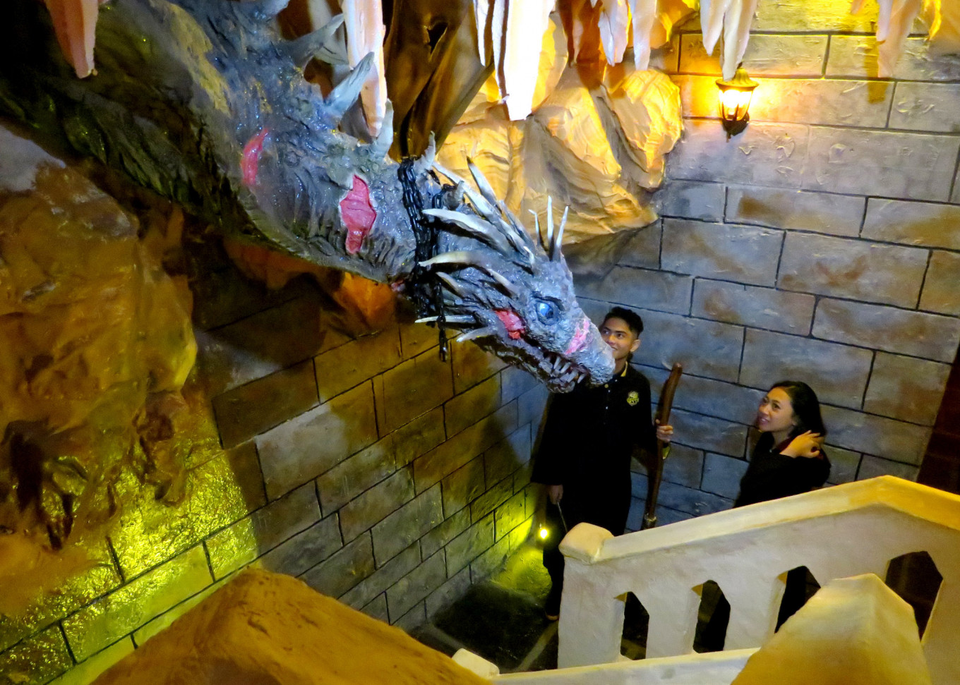 Visitors interact with an animatronic dragon head in one of the Diagon Alley zones.