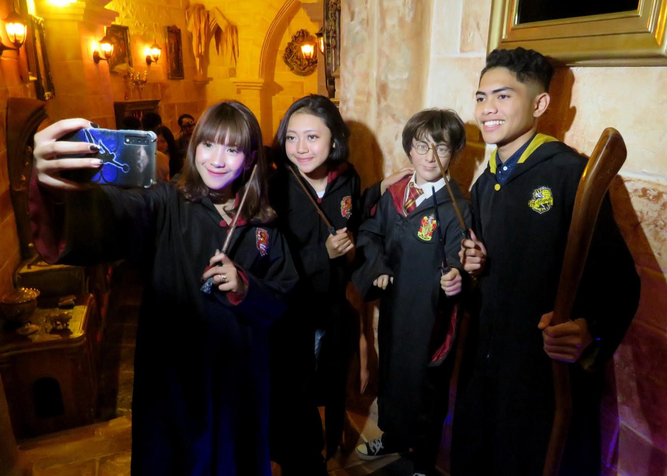 Visitors pose with a Harry Potter wax figure at the Legend Stars Park in Jatim Park 3.