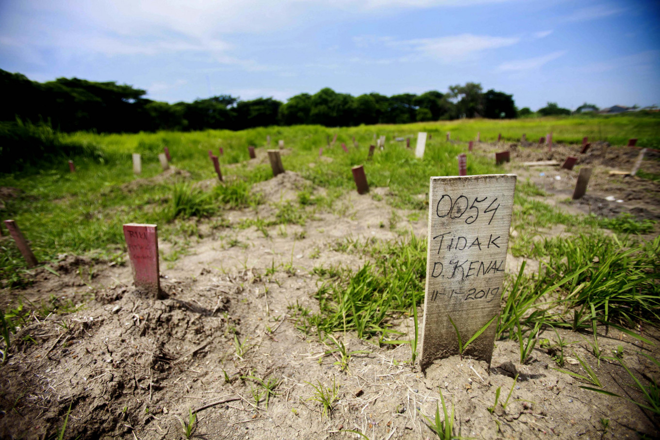 "Unknown: A grave is marked with a wooden plank adorned with the words ""0054 Unidentified 11-1-2019"". JP/Iqbal Yuwansyah"