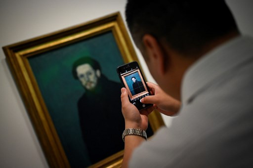 This picture taken on June 14, 2019 shows a man using his mobile phone to take a picture of an oil canvas entitled