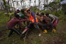 Eight men load teakwood onto a motorcycle. JP/Sigit Pamungkas