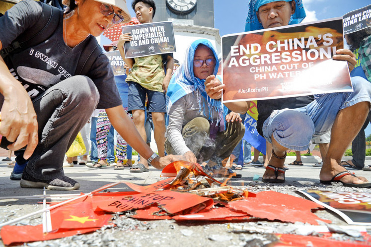 Strong sentiment: Activists burn Chinese flags and display anti-China placards during a protest earlier this year at a park in Manila, after a Chinese vessel sailed away after colliding with a Philippine fishing boat, which sank, in the disputed South China Sea.