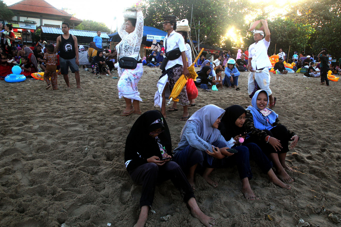 Harmonious: Balinese Hindu adherents clad in white walk by Muslims celebrating tradition on Sanur Beach in Bali. JP/ Zul Trio Anggono