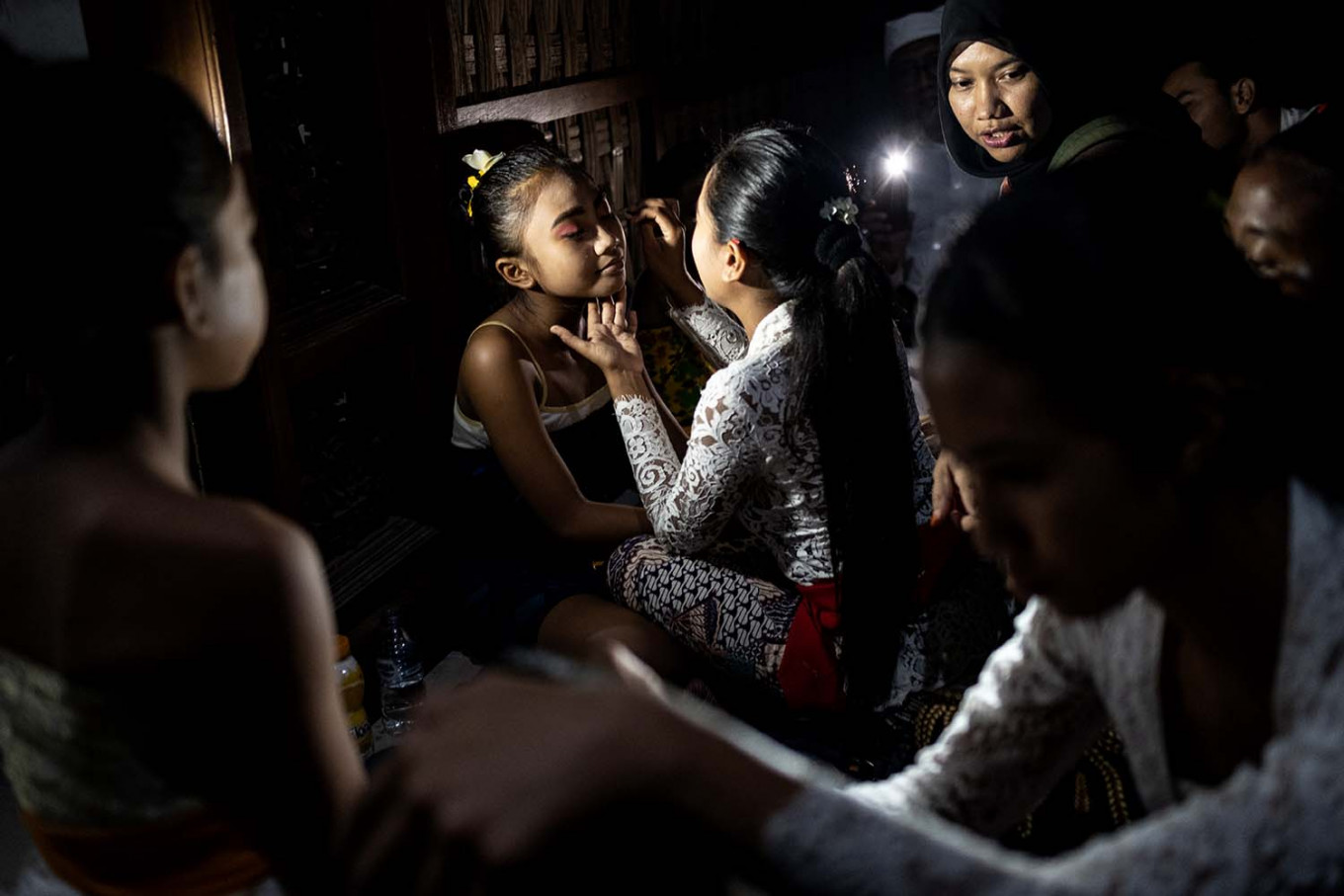 Balinese girls put on makeup as they prepare to perform the Sanghyang Dedari dance during the Api Wali Bhatara Sri ritual to honor the goddess of prosperity before the harvest time in Geriana Kauh village, Selat Duda, Karangasem regency.  JP/Agung Parameswara