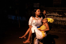 A Balinese woman carries a dancer, who is in a state of trance, during the performance. JP/Agung Parameswara