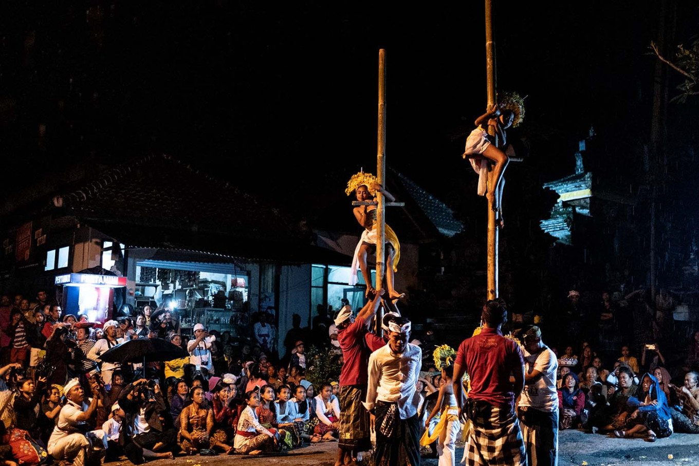 Two dancers climb up bamboo poles during the dance. JP/Agung Parameswara