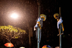 The dancers fearlessly climb up bamboo poles in the rain. JP/Agung Parameswara
