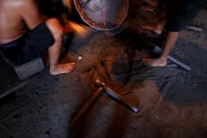 Workers work in the workshop in their bare feet. JP/Maksum Nur Fauzan