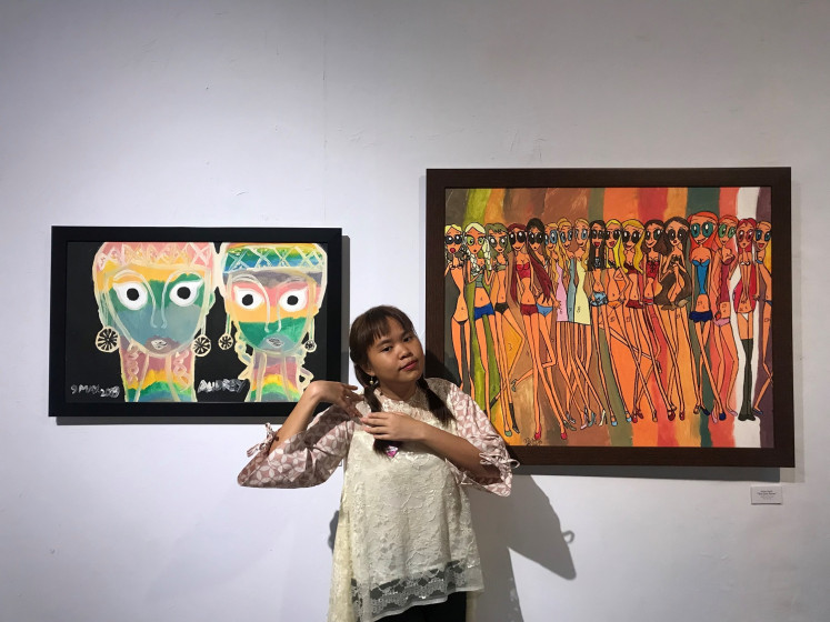 Audrey Angesti with her two paintings, 'The Glow in The Dark Girls' and 'The Girls Power' in the Colors of My World exhibition in Bentara Budaya Jakarta, West Jakarta, on July 4.