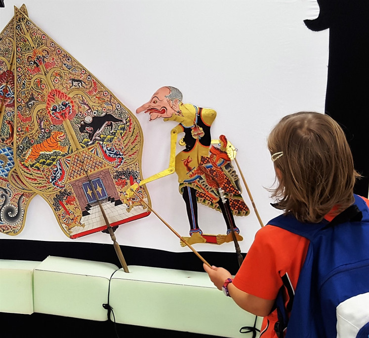 Up close: A student plays with a 'wayang' before puppet master Sumardi packs up the show.