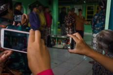 Locals attend and record the wedding ceremony through their mobile phones. JP/Anggertimur Lanang Tinarbuko