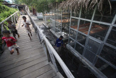 Teach them young: Children run through the heron captive breeding rehabilitation center. JP/Boy T Harjanto
