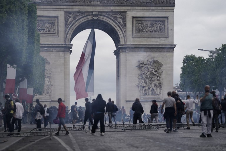 Police fire tear gas to disperse protesters from Champs Elysees after Bastille Day parade