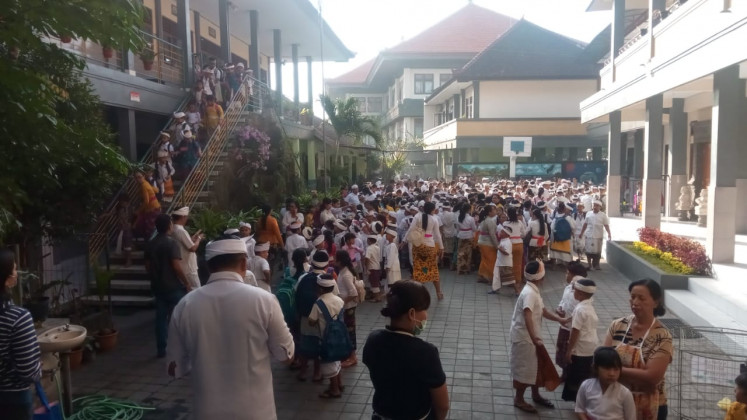 Students of Saraswati 6 Elementary School in Denpasar, Bali run from the school building after