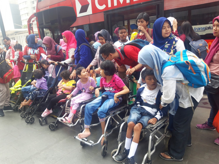 Participants of the walking tour pose for a picture outside the Bundaran HI MRT Station in Central Jakarta on Sunday.