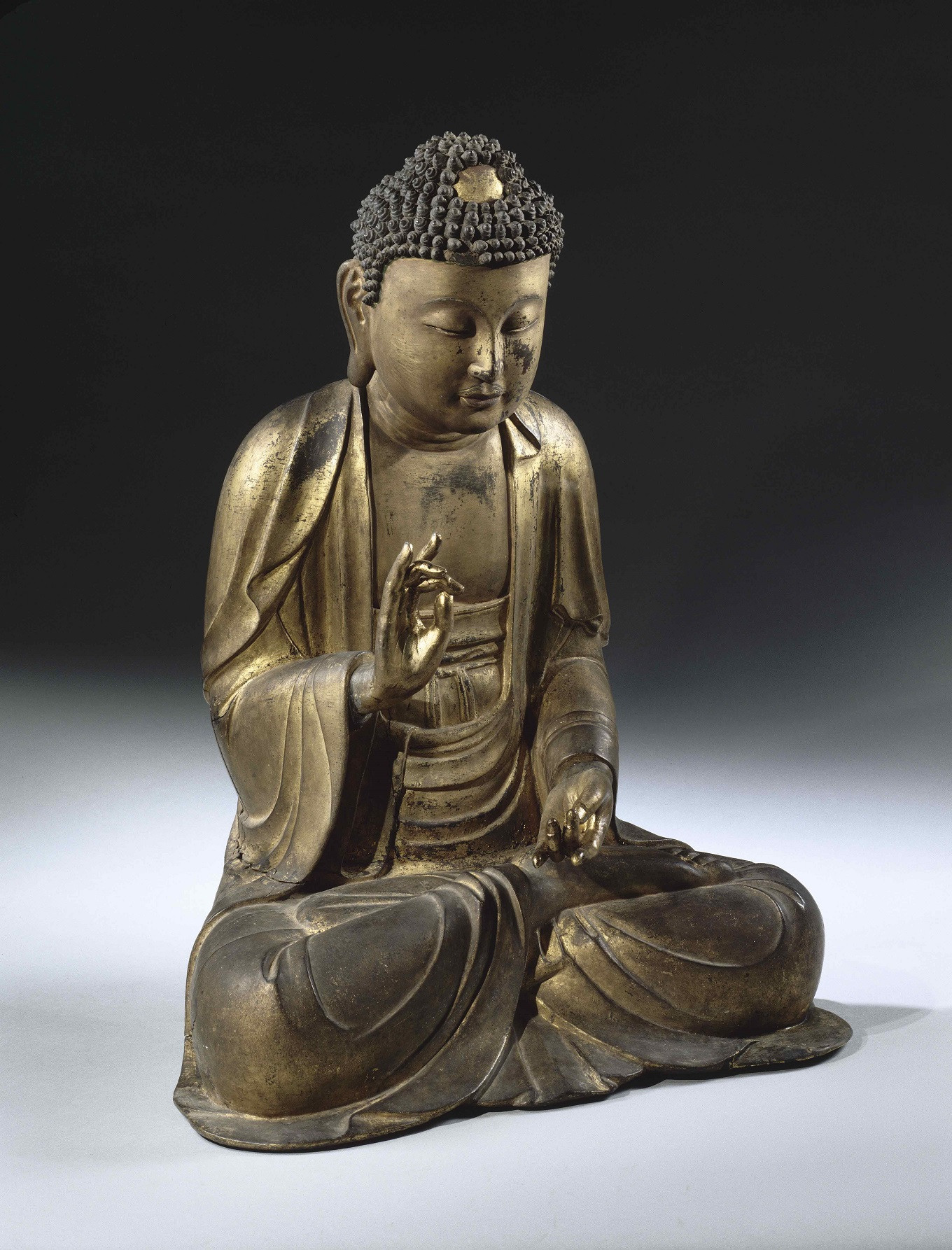The seated Korean Buddha making a gesture of prediction dates from the Koryo period (11th-12th century). The gilded wooden statue is 62 centimeters high, 48 cm wide and 33 cm thick and was collected by the Charles Varat Mission in 1888.