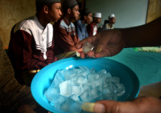 Ubaidillah gives an ice cube to one of his students after praying for him. JP/Aman Rochman