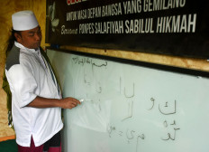Ubaidillah Hamid teaches his students to read the Quran at the boarding school, home to 22 teenagers who are former drug addicts. JP/Aman Rochman