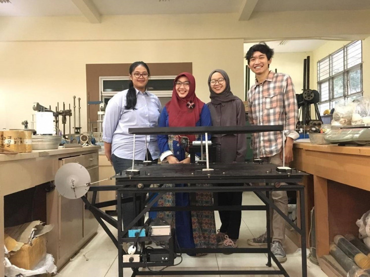The team from Gadjah Mada University's vocational engineering school pose in front of their spring damper foundation invention. The team comprises  Yosi Kristiana (left), Siti Zuliana (second right) and Miftahussurur Rosyadi (right) while Devi Oktaviana Latif is their supervising lecturer.