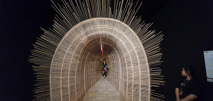 A walk through time: A visitor walks through a tunnel-shaped bamboo art installation titled 'Bubu Waktu' (Time Trap) by Sunaryo at ARTJOG, which is being held at the Jogja National Museum in Yogyakarta.