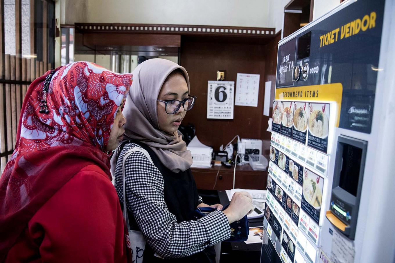 Two Indonesian Muslims are choosing halal ramen from a vending machine. JP/Rosa Panggabean