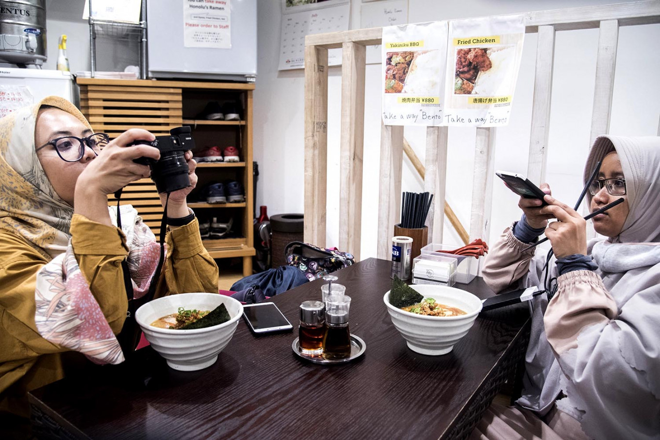 Two Indonesian Muslim tourists are taking picture of their halal ramen. JP/Rosa Panggabean