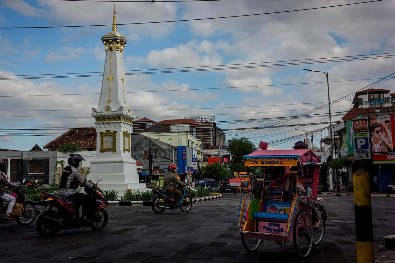Sutopo drives his pedicab while passing the iconic Tugu Yogyakarta. JP/Anggertimur Lanang Tinarbuko