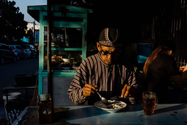 Before working, Sutopo eats breakfast at a nearby food stall. JP/Anggertimur Lanang Tinarbuko